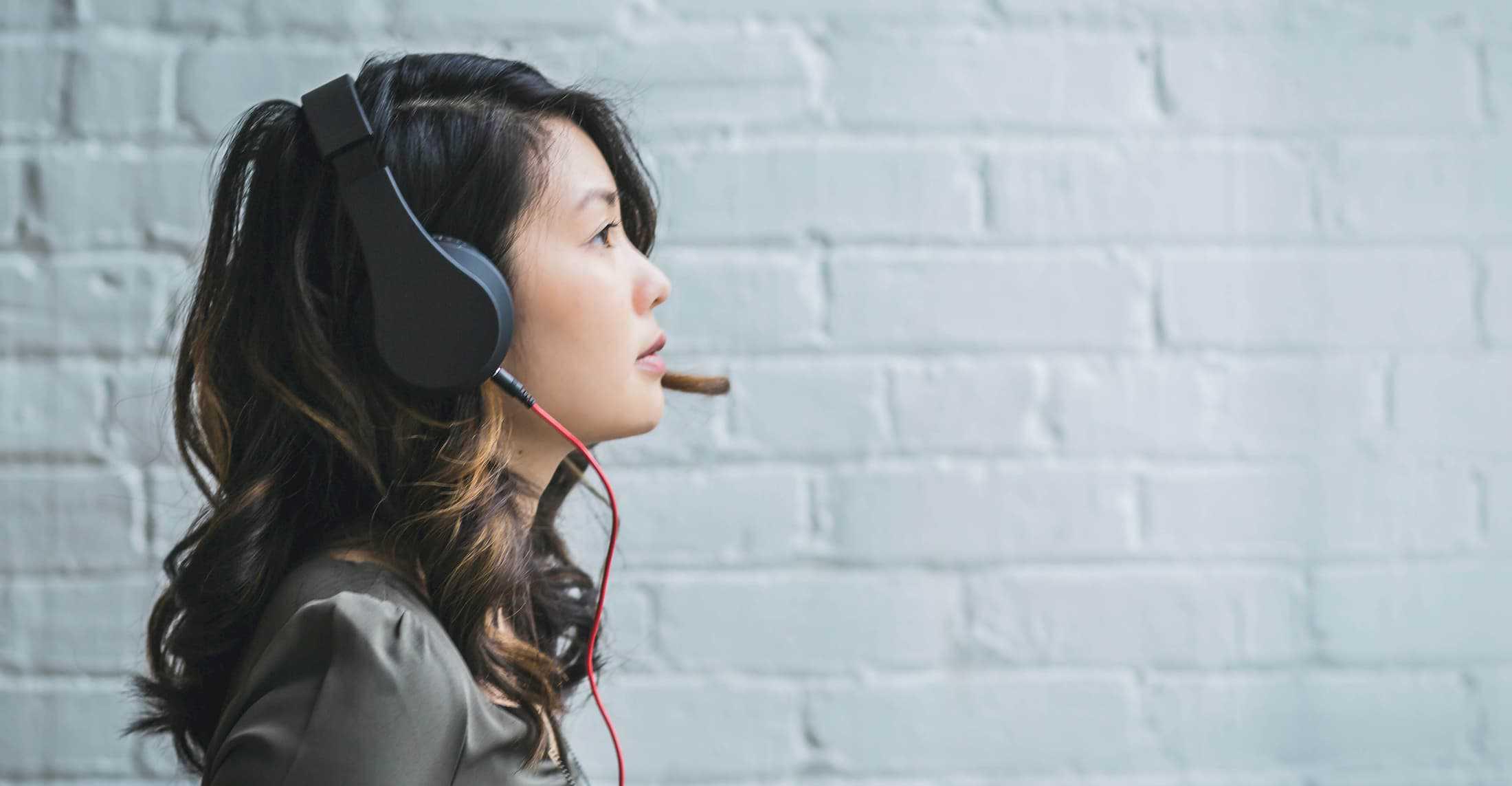 Woman wearing headphones listening for ielts test
