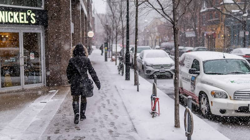 person walking by the street on a chilly Canadian  Weather