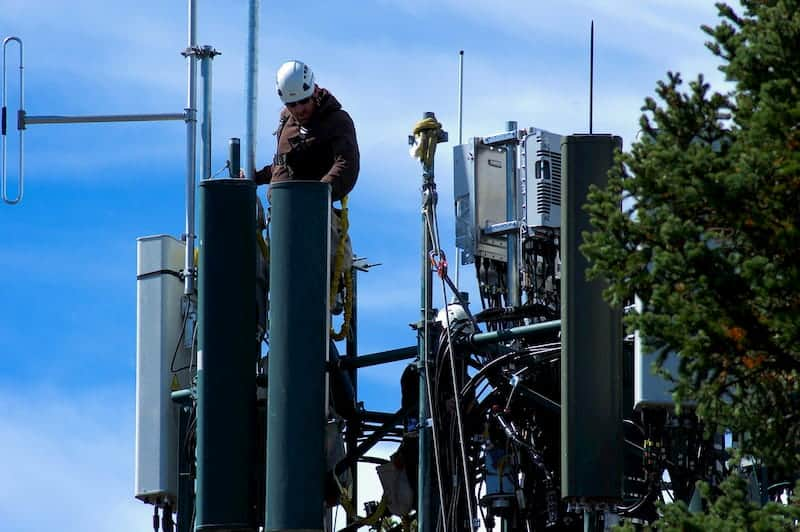 MAN FIXING A CELL TOWER REASONS FOR HIGH PRICES OF CELLPHONE PLANS IN CANADA